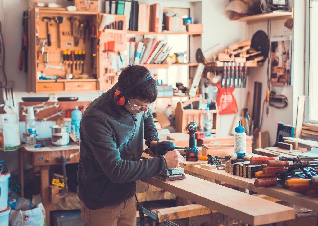 man in heaset doing woodwork