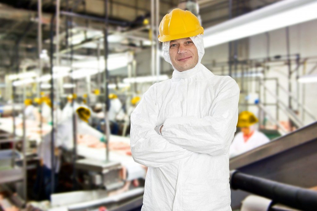 Smiling worker in a meat processing factory and slaughterhouse, wearing hygienic clothing