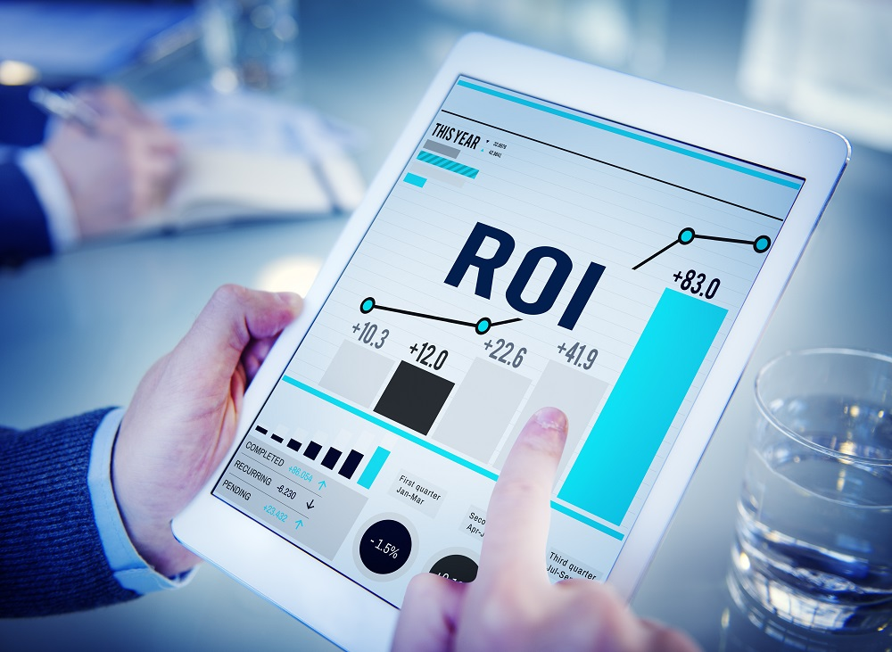 man pushing bars on ROI chart on tablet