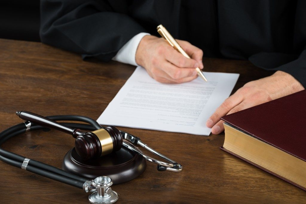 person signing a document near gavel