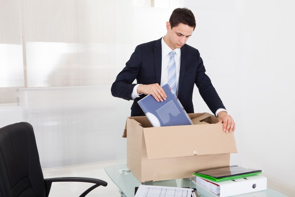 Sad young businessman packing files in cardboard box at desk in office