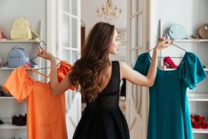 woman in a store trying out two dresses