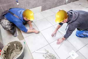 construction workers tiling a bathroom