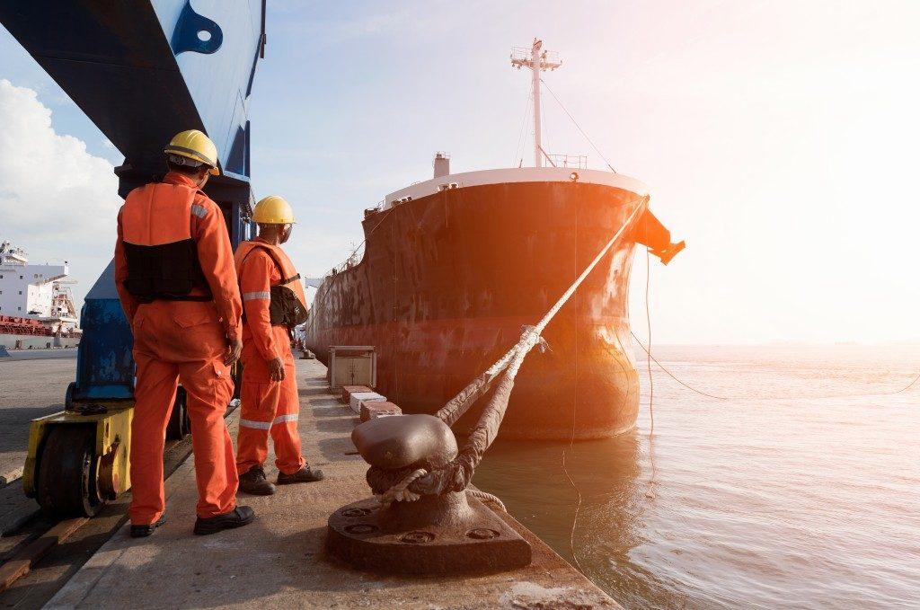 men guiding the cargo ship to the dock