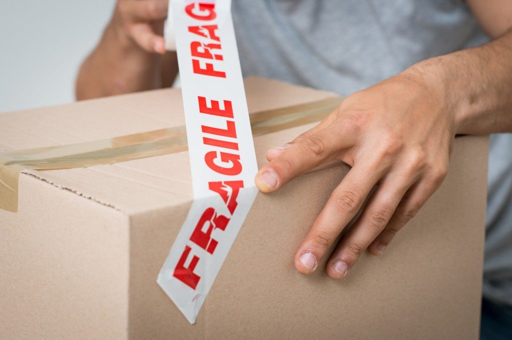 person putting a fragile sticker labe in the package