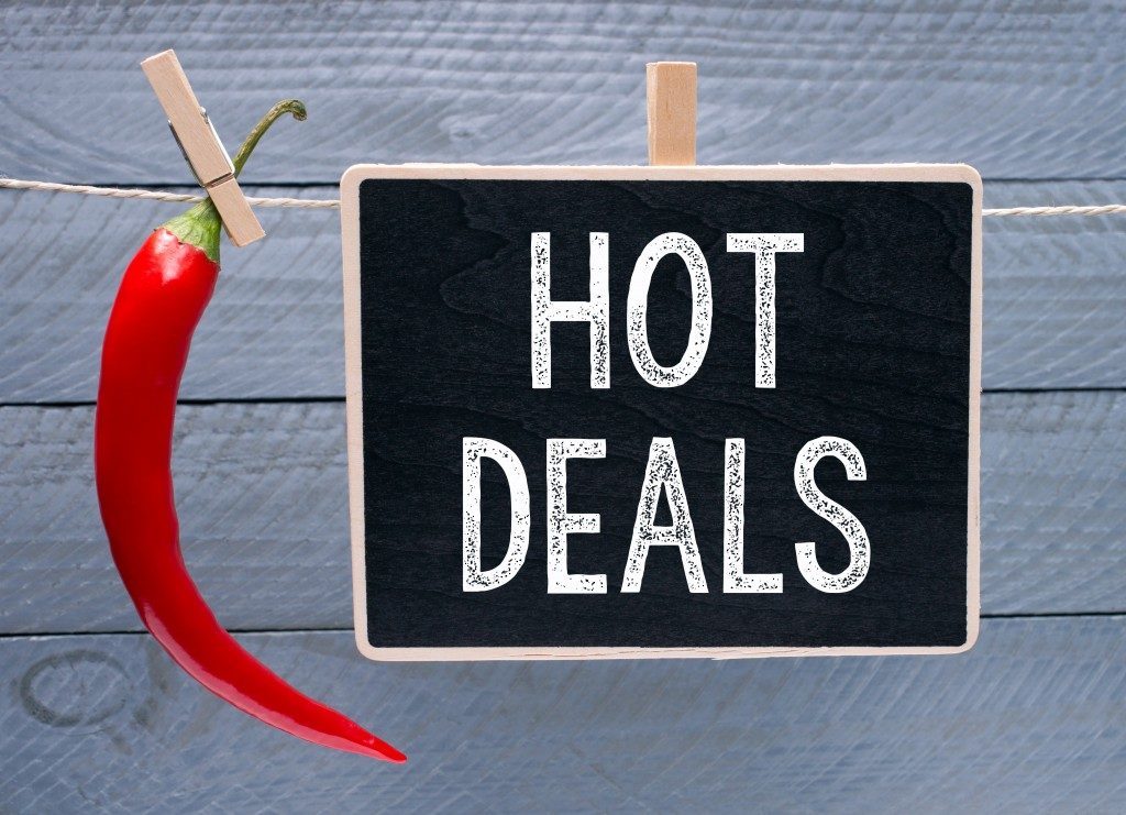 Hot Deals - red hot chili with chalkboard and text on wooden background