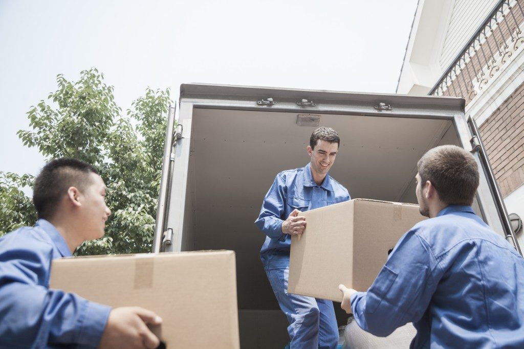Movers carrying boxes into van