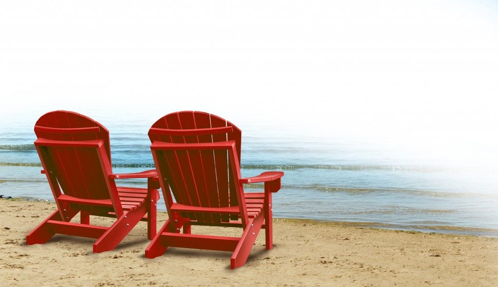 adirondack chairs on a tropical sandy beach with ocean view