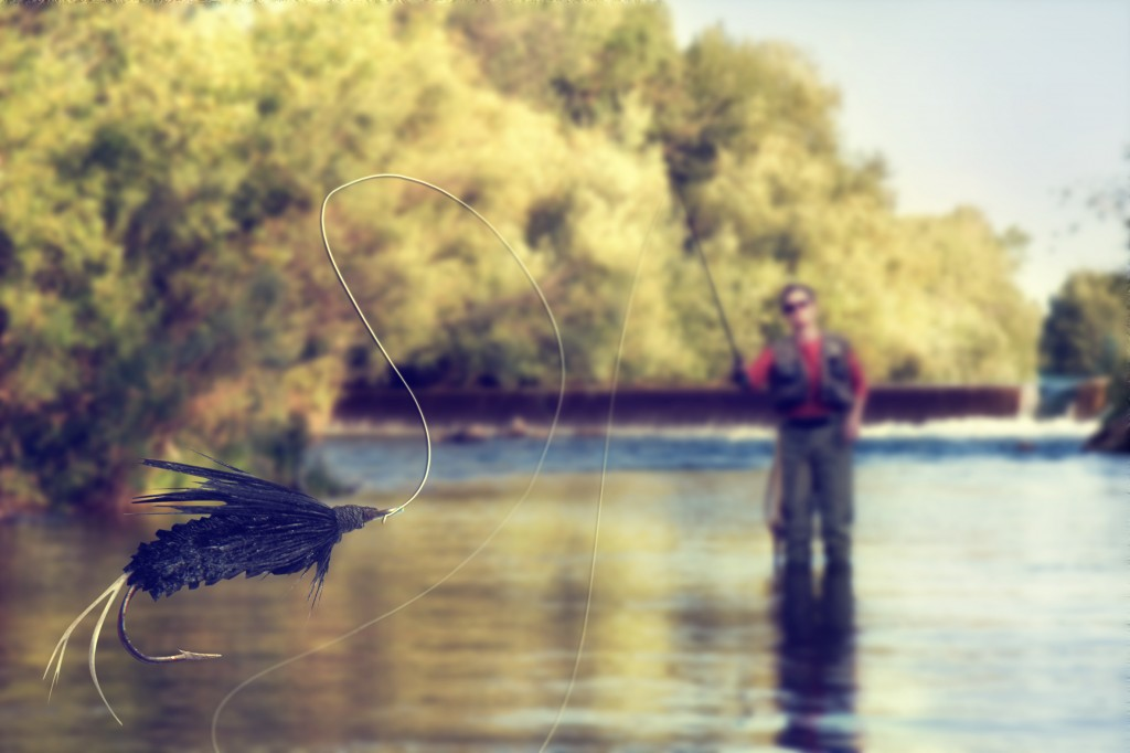 a person fly fishing in a river with a fly in the foreground