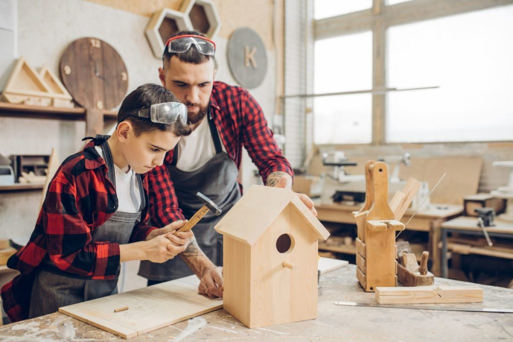man teaching son how to build a bird house