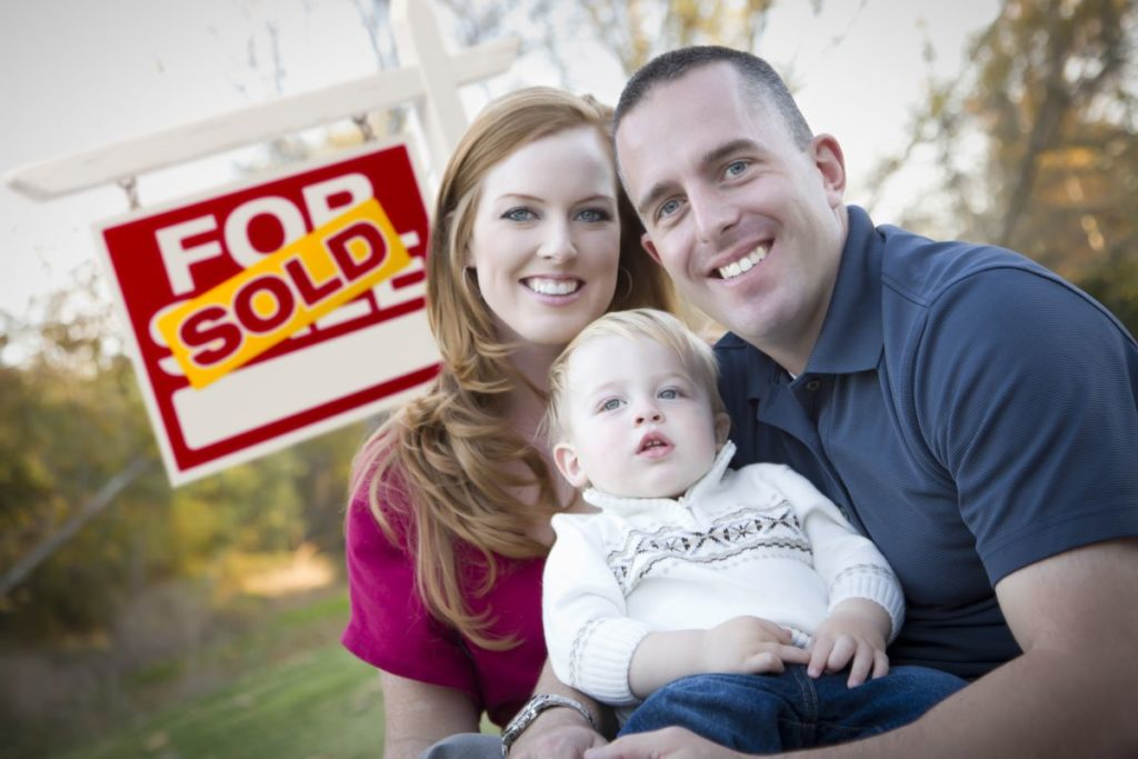 family in front of sold sign for sale