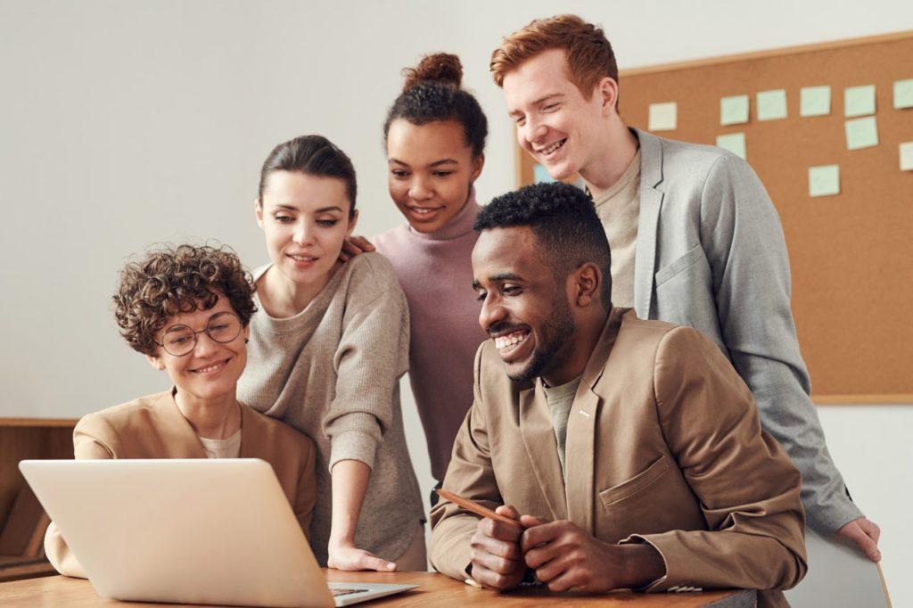 employees smiling at laptop presentation