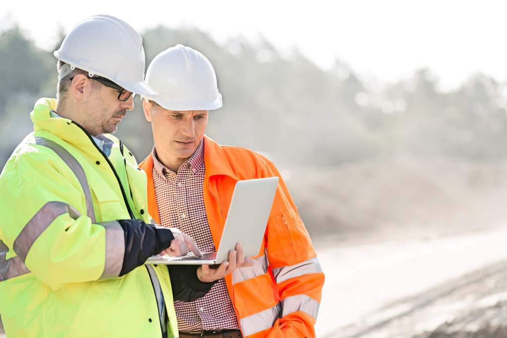 Construction workers using a laptop