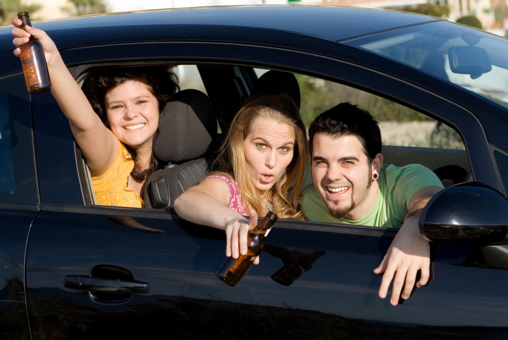 people drinking alcohol in the car